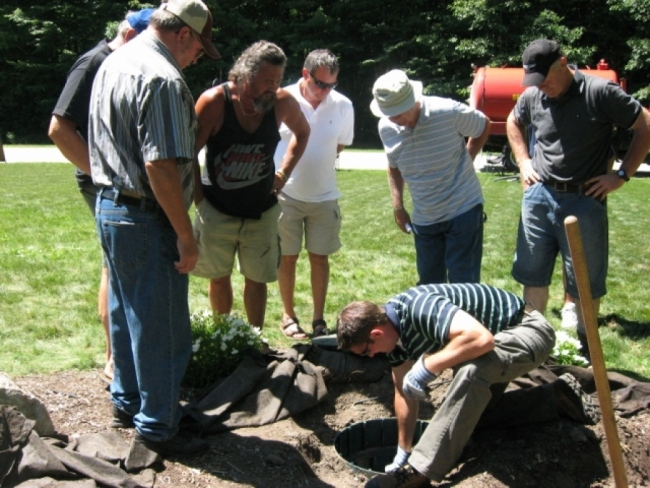 A team of workers digging out and inspecting a septic system